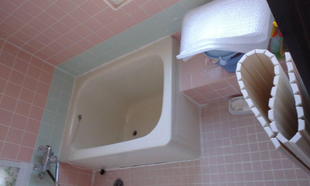 ピンク色のタイルが貼られた古い浴室