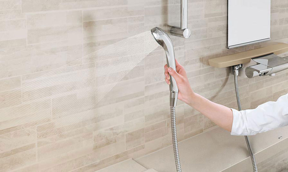 浴室の壁をシャワーで掃除している人