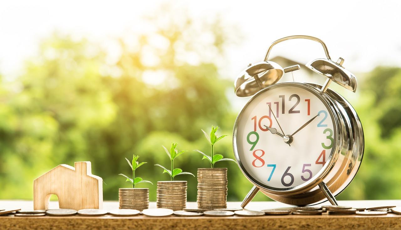 時計の隣で貯金を積み上げる